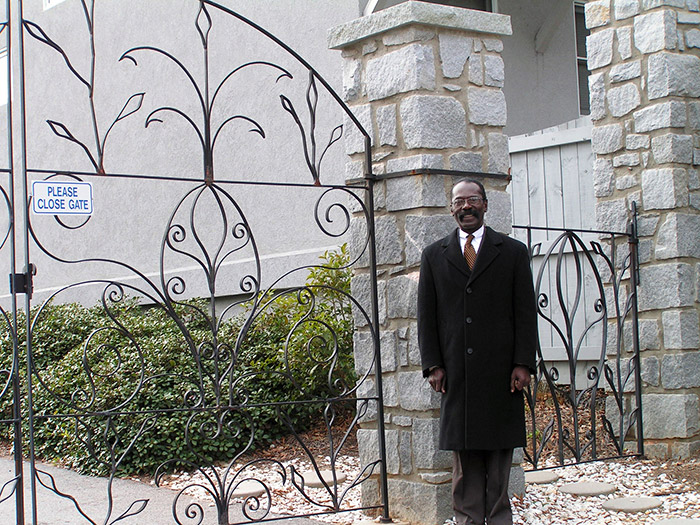 Councilman Davis at a hand-made ornamental gate by black craftsmen, Columbia Historic Sites
