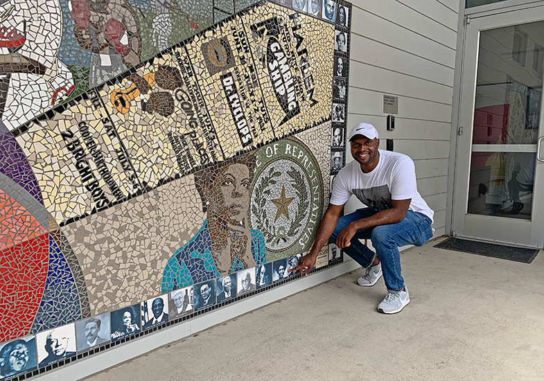Austin Tours' Javier Wallace at Rhapsody in Austin mural aside African America Cultural Facility